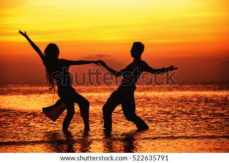Silhouette of hot dancing couple at golden tropical sea sunset background.