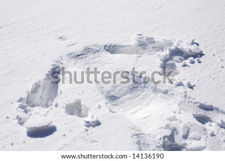 silhouette of human body imprint on soft snow surface