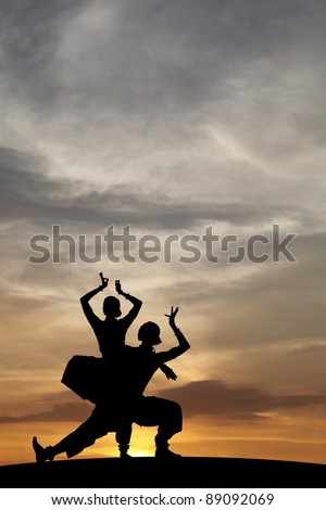 Silhouette of Indian cultural classical dancer posing on a hill against a surreal dramatic sunset sky. - stock photo