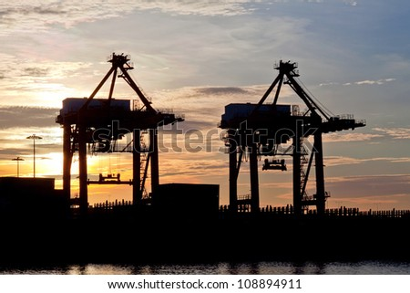 silhouette of Industrial ship in Terminal port with sunrise