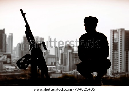Silhouette of infantry soldier with machine gun sitting to guard on blur citscape background