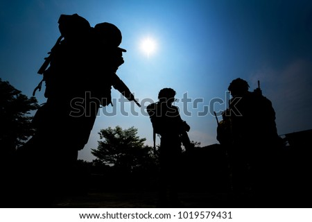 Silhouette of infantry soldiers team with blue sky background