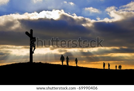 Silhouette of Jesus Christ crucifixion on cross on Good Friday Easter with people walking up hill towards Jesus - stock photo