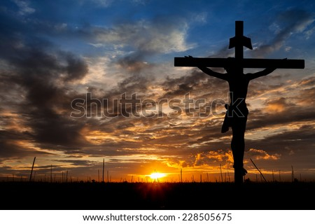 Silhouette of Jesus with Cross over sunset concept for religion, worship, Christmas, Easter, Redeemer Thanksgiving prayer and praise. - stock photo