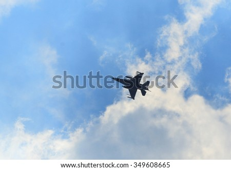 Silhouette of jet-fighter   against the sky - stock photo