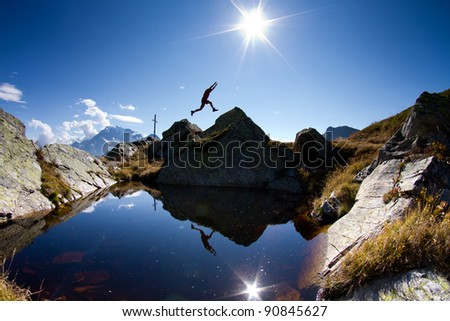 silhouette of jump on top of mountain - stock photo