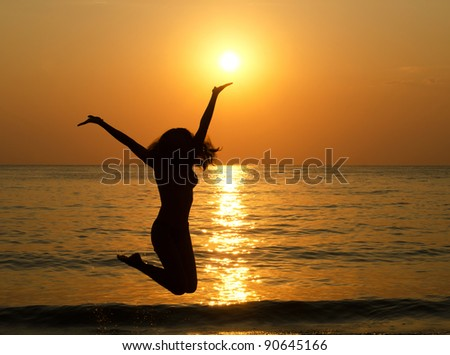 Silhouette of jumping girl against a decline - stock photo