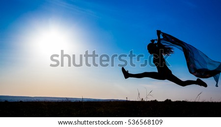 silhouette of  jumping girl on hill against sunrise