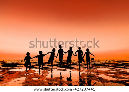 Silhouette of jumping group kid, people stand on beach with warm tone - stock photo