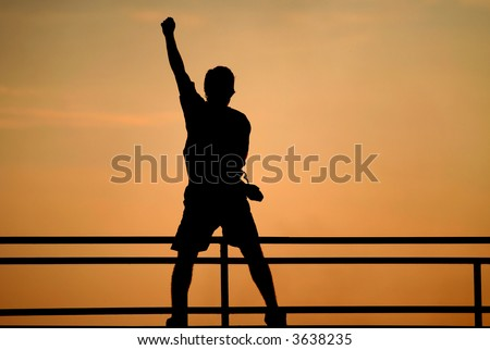 Silhouette of jumping man. victory concept. Happy man with raised hand - stock photo