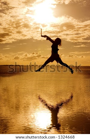 Silhouette of jumping woman holding a laptop computer.
