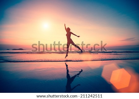 Silhouette of jumping woman on the beach at sunset. - stock photo