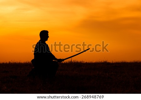Silhouette of kendo fighter holding bokuto - stock photo