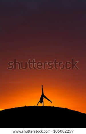 silhouette of kid doing a cartwheel in sunset - stock photo