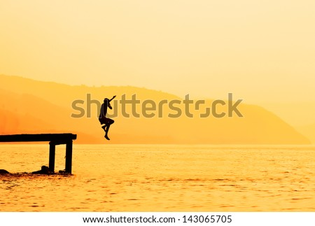 Silhouette of kids jumping from river dock, at sunset. - stock photo