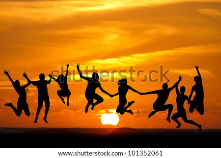 silhouette of kids jumping on beach in sunset