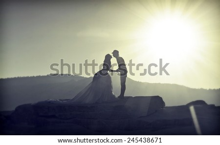 Silhouette of kissing a bride and groom at sunset - stock photo