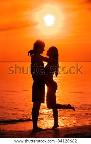 Silhouette of kissing young couple against sea sunset. - stock photo