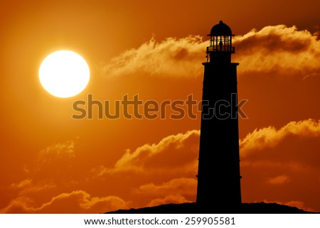 Silhouette of lighthouse above the sunset, sun, sunlight, sunrise Seascape with lighthouse at sunset - stock photo