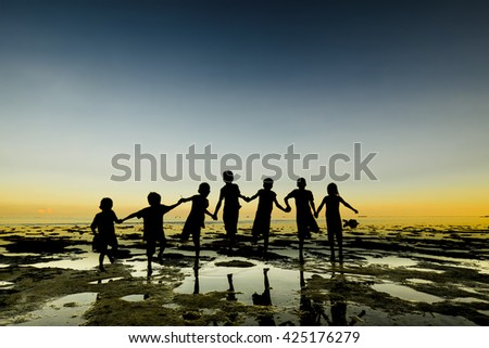 Silhouette of lineup group of kid, people stand on beach with water reflection - stock photo