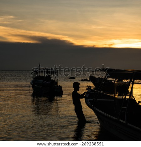 silhouette of little boat and seaman in the sea, sunset time - stock photo