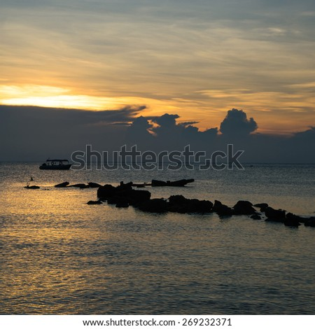 silhouette of little boat in the sea, sunset time - stock photo