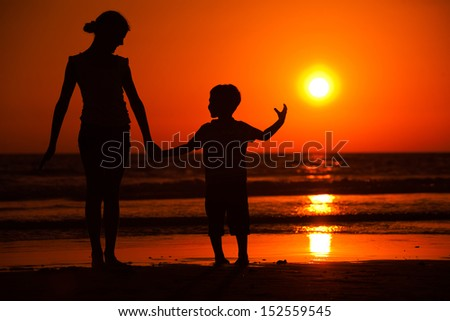 Silhouette of little brother and sister playing at the beach during sunset - stock photo