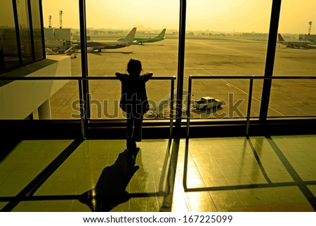 Silhouette of little girl at airport window - stock photo