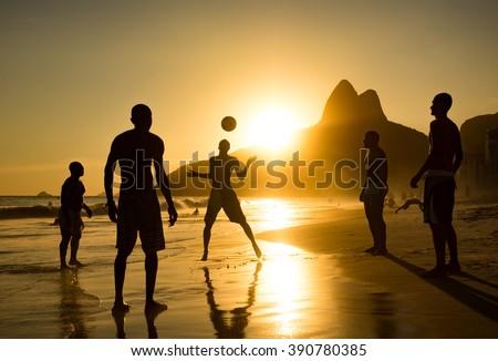 Silhouette of locals playing ball at sunset in Ipanema beach, Rio de Janeiro, Brazil. - stock photo