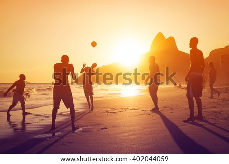 Silhouette of locals playing ball at sunset in Ipanema beach, Rio de Janeiro, Brazil. - stock photo