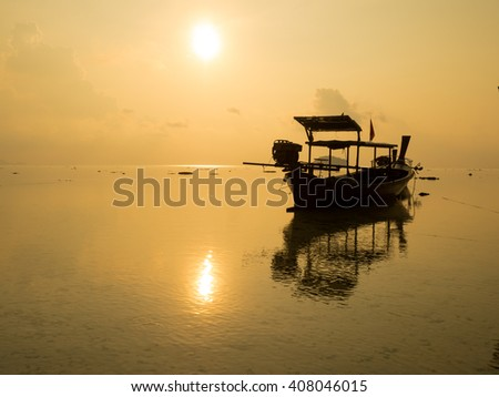 Silhouette of long tail fishing boat reflect with water sea at beach, sunrise in Thailand.