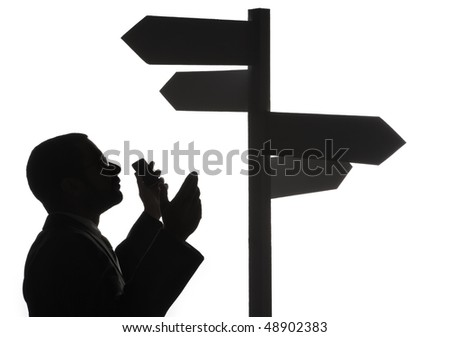 Silhouette of lost businessman with mobile phone looking at blank multiple directional sign, isolated on white background. - stock photo