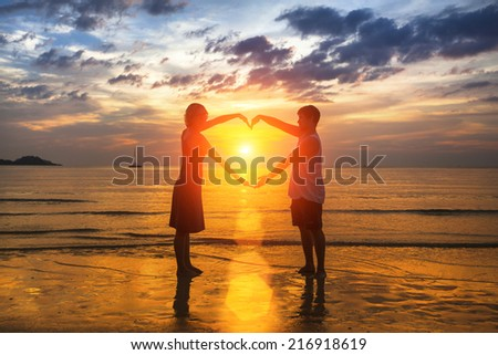 Silhouette of loving couple during an amazing sunset, holding hands in heart shape. - stock photo