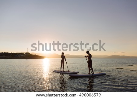 Silhouette of male and female on sup surf swimming at the ocean. Concept lifestyle, sport, love