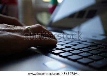 Silhouette of male hand pressing black keys on the laptop keyboard  - stock photo