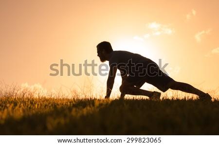 Silhouette of male runner at start.  - stock photo