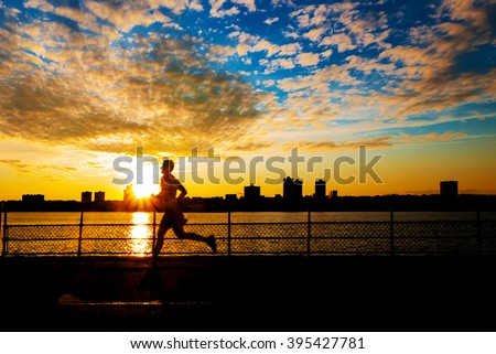 Silhouette of male runner at sunset along Hudson River on west side of Manhattan - stock photo
