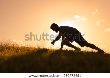 Silhouette of male runner looking at his stop watch. - stock photo