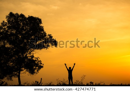 Silhouette of man and beautiful sky sunset. hand up of success.
