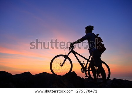 Silhouette of man and his bike on rock mountain with sunrise twilight background.  - stock photo