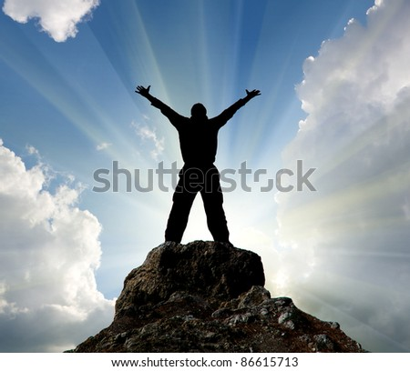 Silhouette of man and sunshine on sky background. Man standing on top of a mountain. greatness concept.
