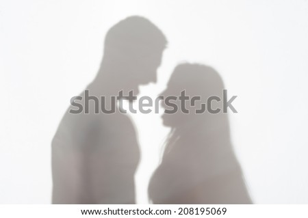 Silhouette of man and woman standing on white background and quarrelling - stock photo