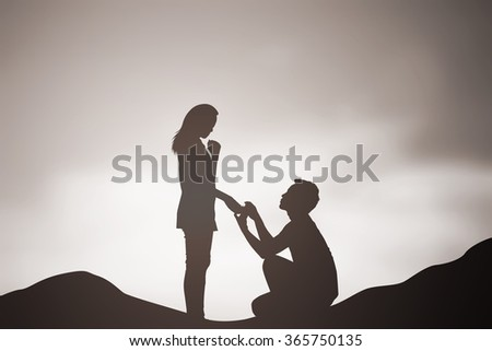 silhouette of man ask woman to marry on sea beach mountain background:teen couple in love concept:dark shadow of people lovers in romantic and happy moment time.Valentine's day:sepia color tone effect - stock photo