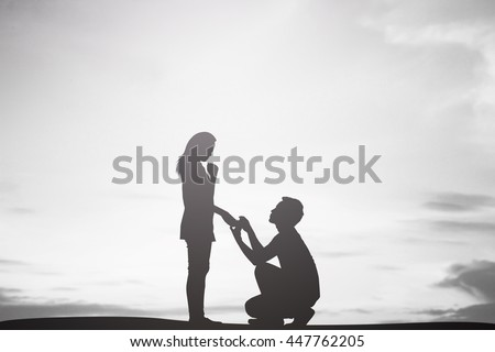 silhouette of man ask woman to marry on sky sepia color tone background:teen couple in love concept:dark shadow people lovers in romantic and happy moment time.Valentine's day. - stock photo
