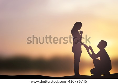 silhouette of man ask woman to marry on sunset hours background:adult couples passion in love concept:dark black shadow of people lovers in romantic and happy moment time conceptual.Valentine's day - stock photo