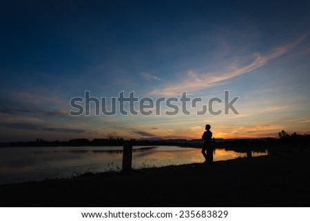 silhouette of man at sunset in the dam - stock photo