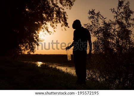 Silhouette of man at sunset with bottle of alcohol in bushes - stock photo