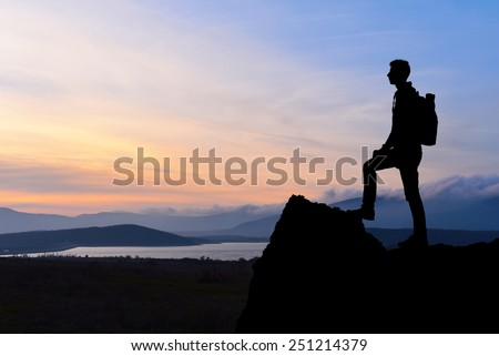 Silhouette of man at the top of the mountain on sunset. Beautiful landscape.