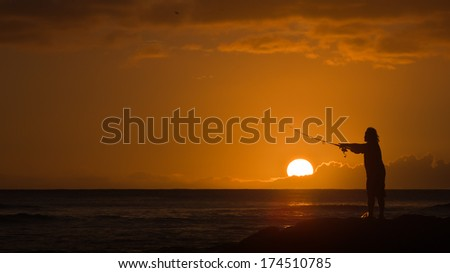 Silhouette of Man Casting a Fishing Rod with Round Orange Setting Sun off the Coast of Honolulu, Hawaii - stock photo