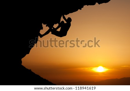 silhouette of man climbing on overhanging rock - stock photo